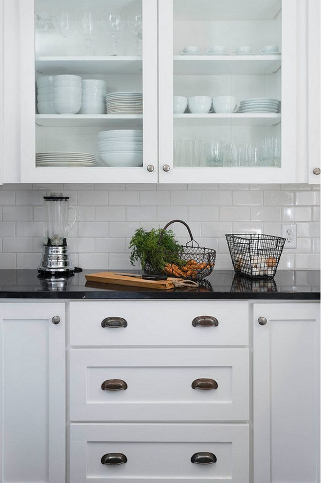 Simple farmhouse kitchen with white cabinet black granite countertop subway tile backsplash and glass door upper cabinets also ideas