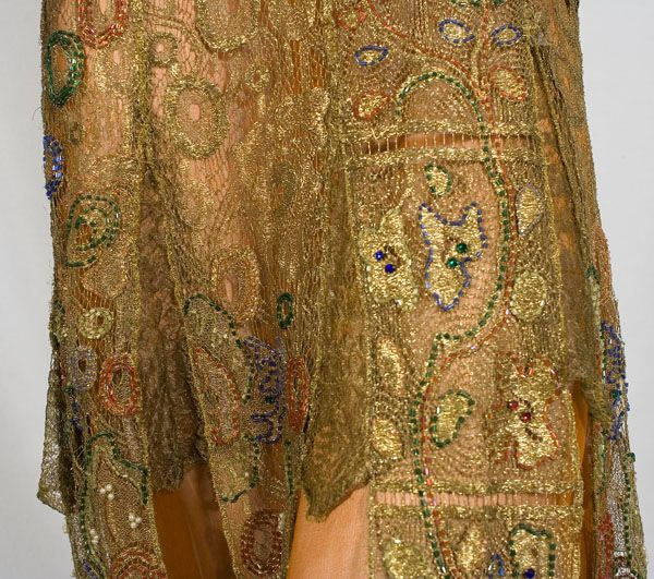 Jeweled metallic lace evening ensemble, c.1925. The cape and dress are fashioned from gold metallic lace. The lace is embellished with jewel-tone glass beads and faux pearls. Detail