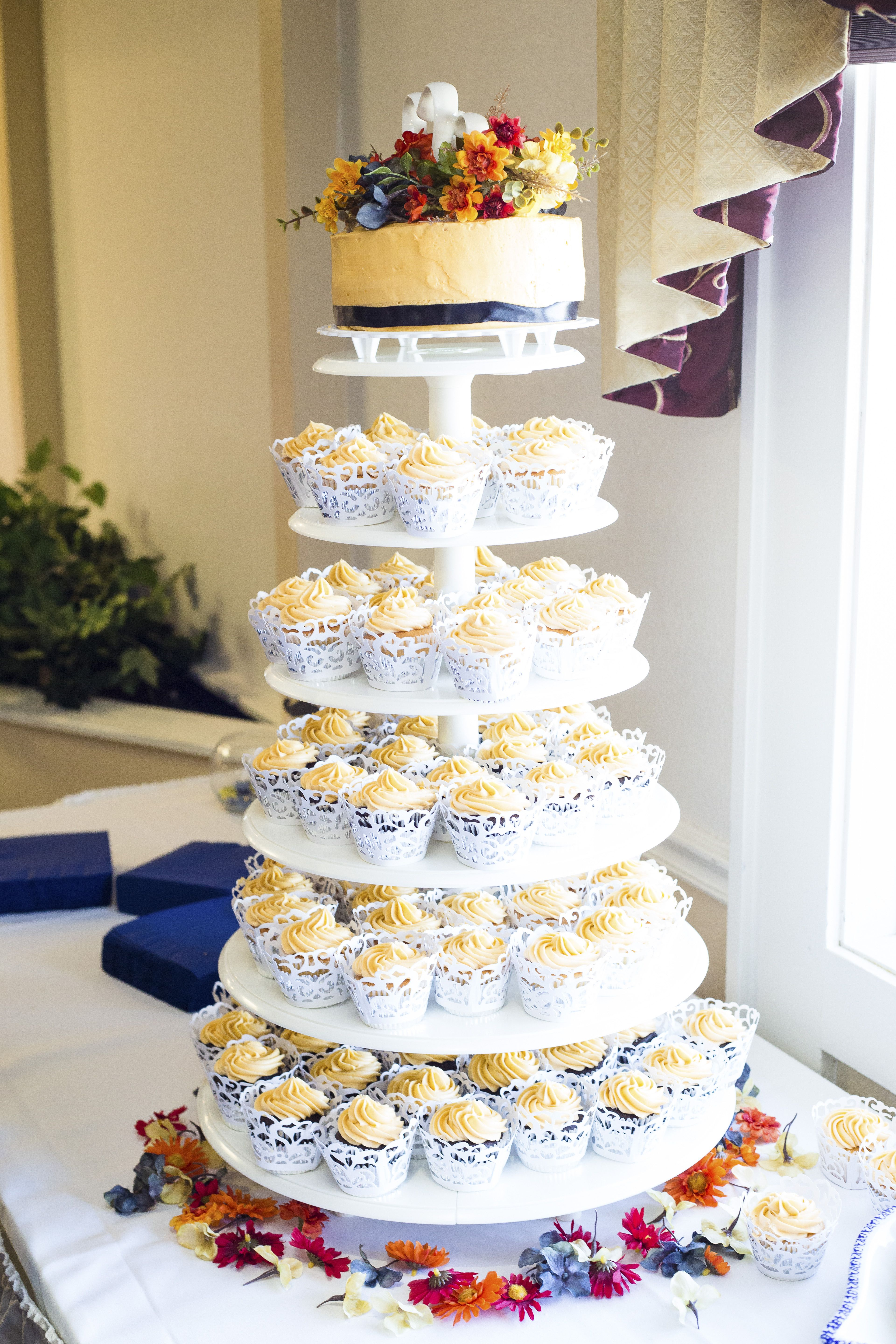 Naked cake and cupcakes with fruit topper, placed on a