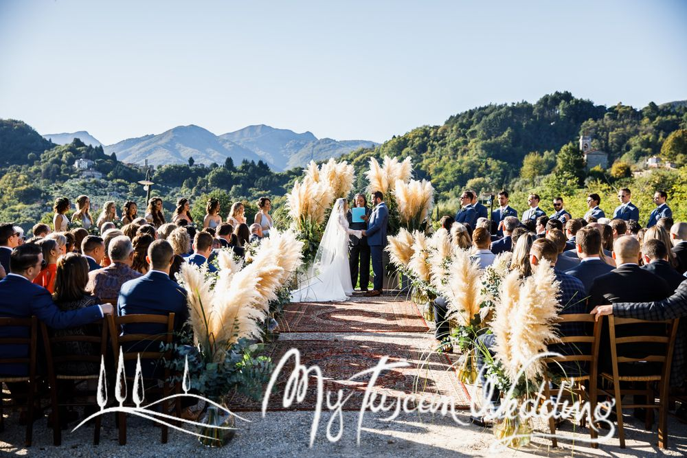 Pampas grass and eucalyptus framed ceremony with Persian carpets and wine damigian accents. Rustic chic wedding.