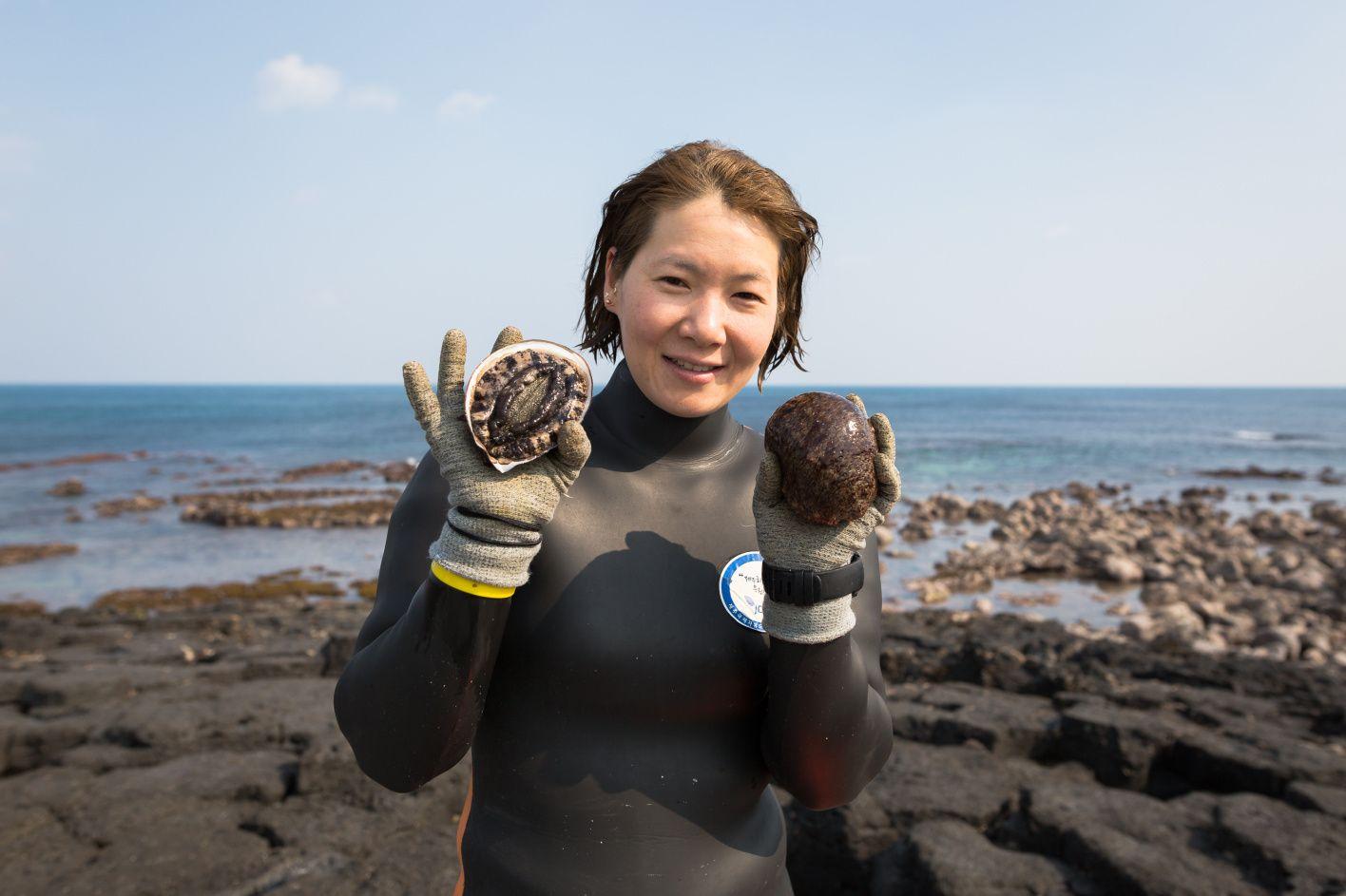 Elderly Japanese women of the sea dive for shellfish in