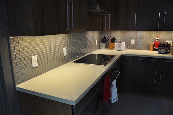 Modern concrete countertop with tile backsplash.