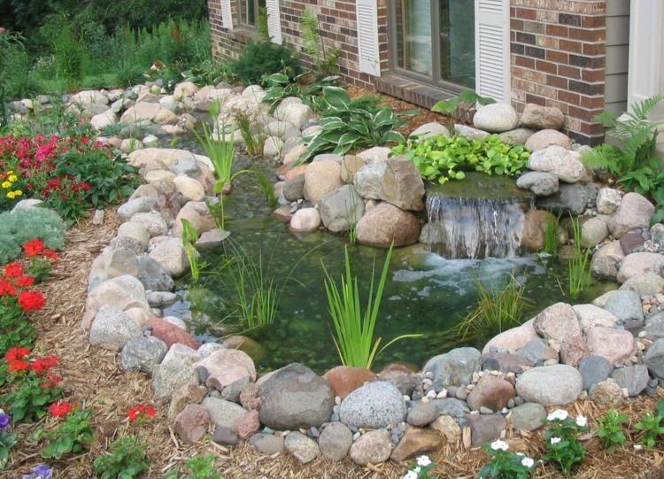 Ein Gartenteich mit Bachlauf und Wasserfall umrahmt von Steinen ...