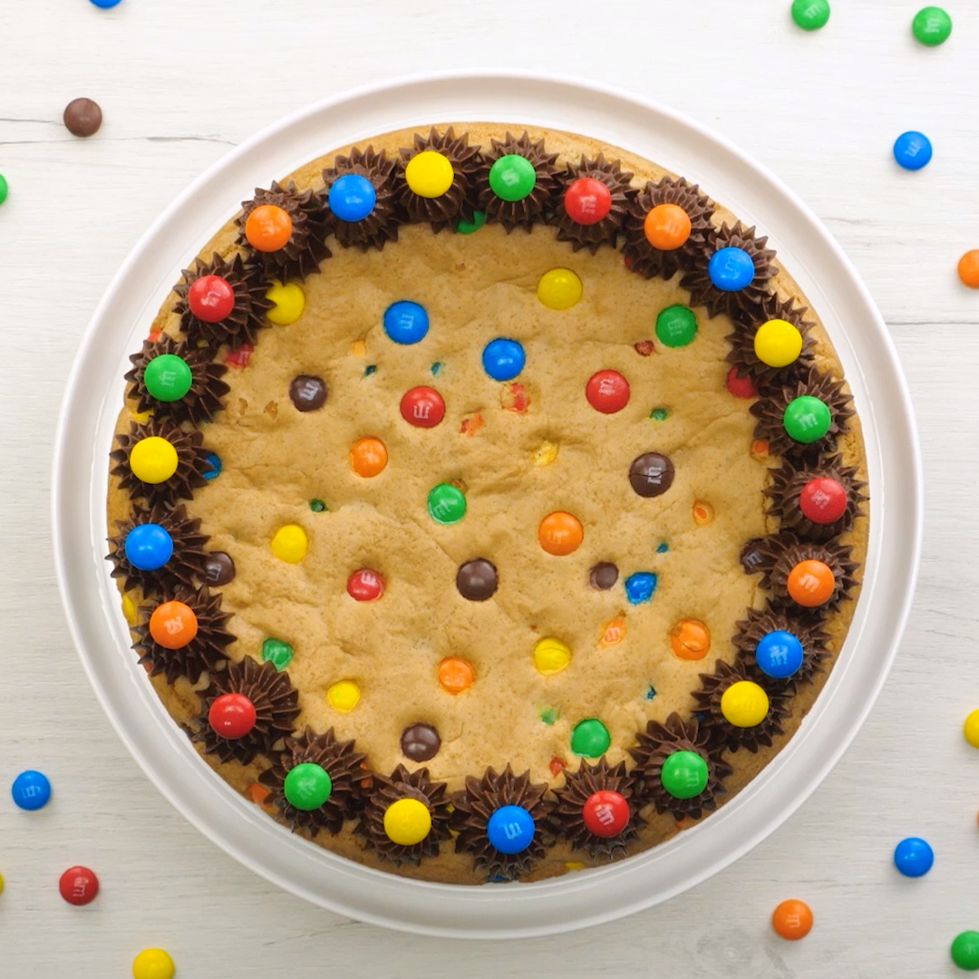 This M&M's Cookie Cake Recipe is a fun and easy dessert recipe the whole family will enjoy. A giant cookie made with M&M's and chocolate frosting for even more deliciousness!  cookie  cookiecake  mms  dessert  cake  chocolate