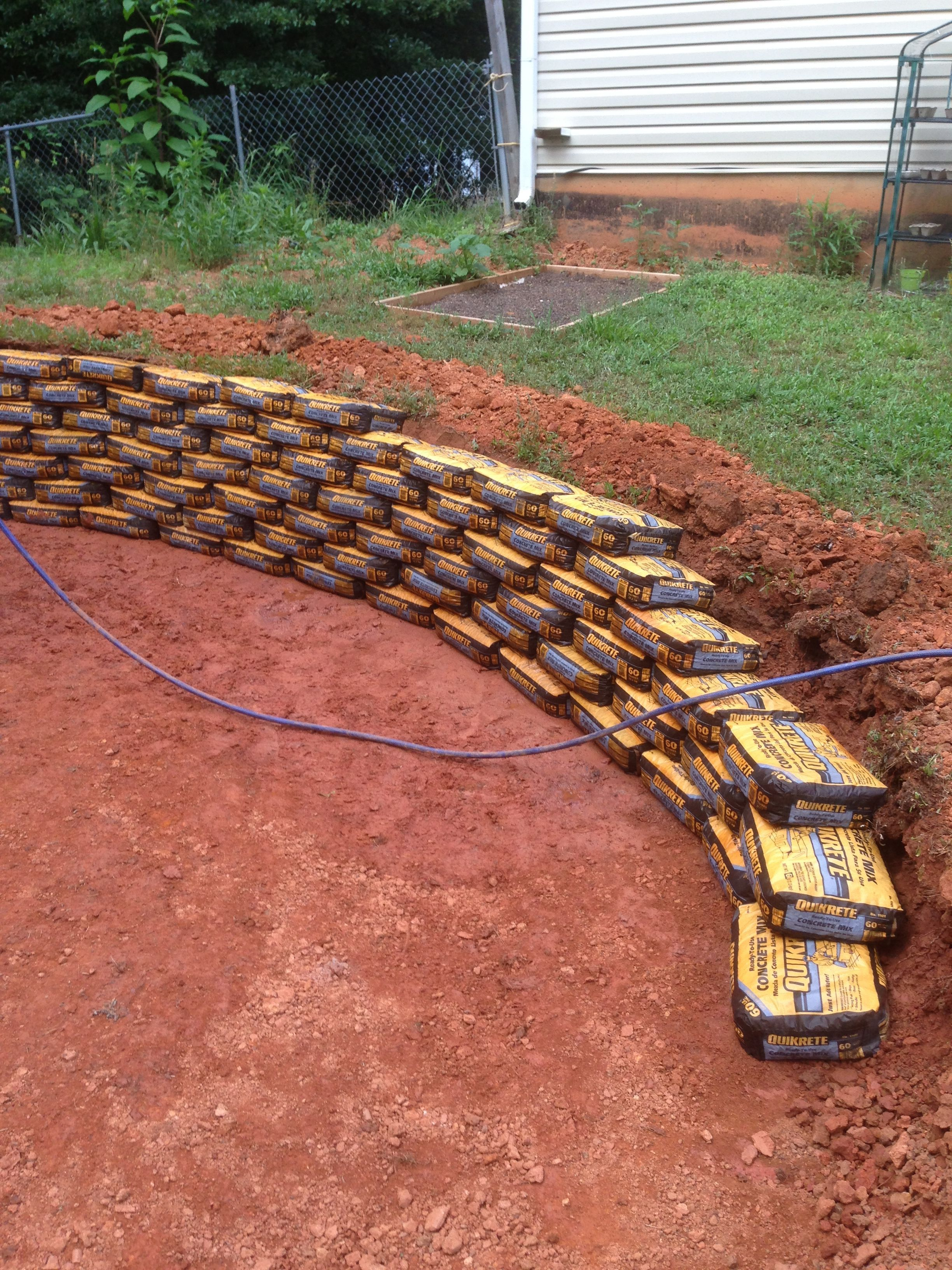 Make A Retaining Wall Using Quickcrete Bags Unopened And Stacked Like Bricks Wet The Bags Daily Concrete Retaining Walls Diy Retaining Wall Backyard Landscaping