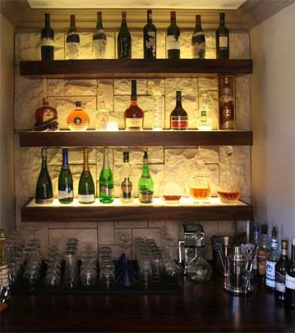 cool liquor display with stone wall background | Bar ...