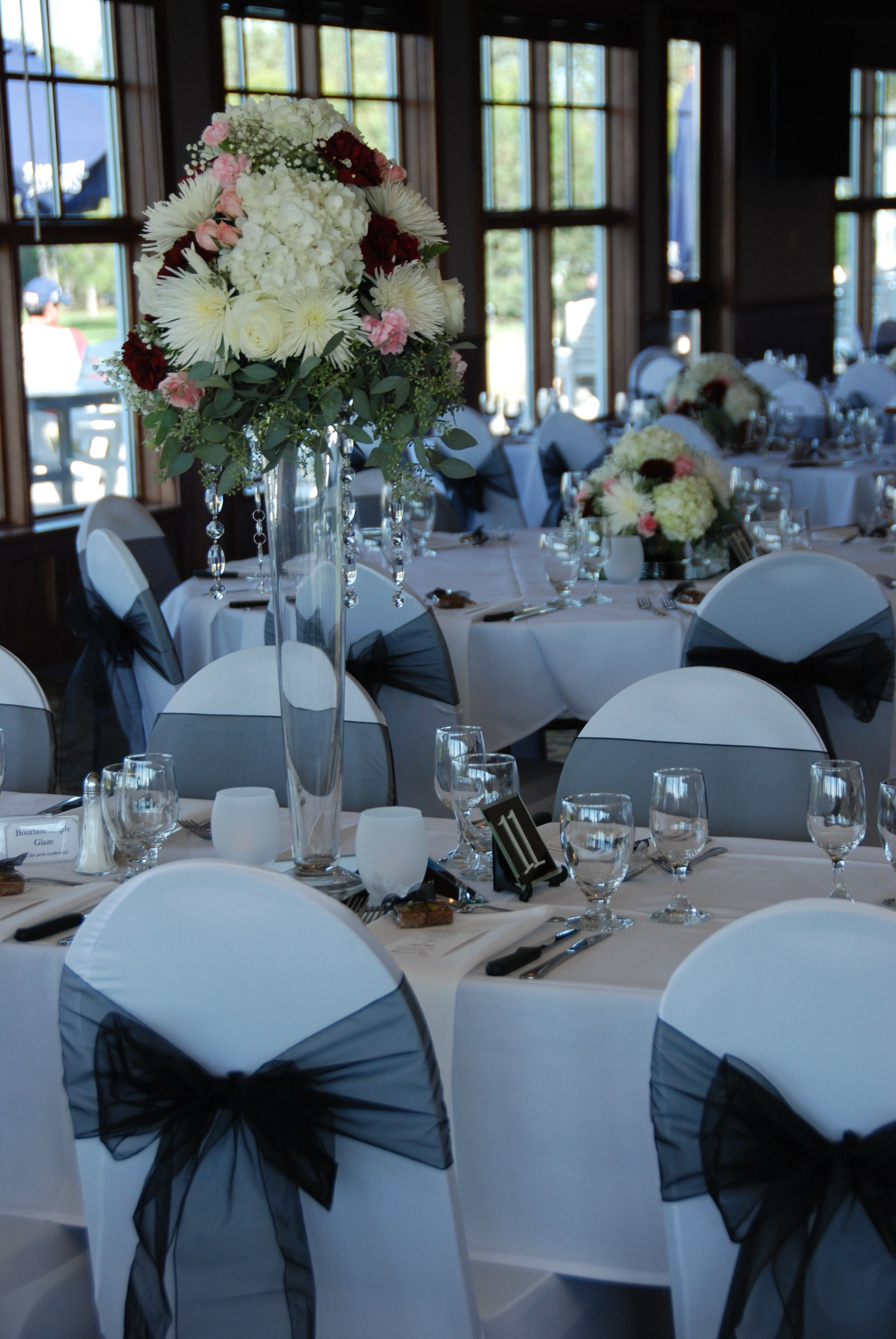 Blue and black wedding decor  White chair covers black organza sashes high and low bouquets