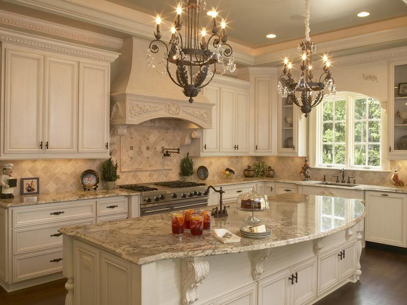 Elements of a French Country kitchen: Glazed painted cabinets, Arched  window, Corbels under the island and range hood all add to the feel and  style.