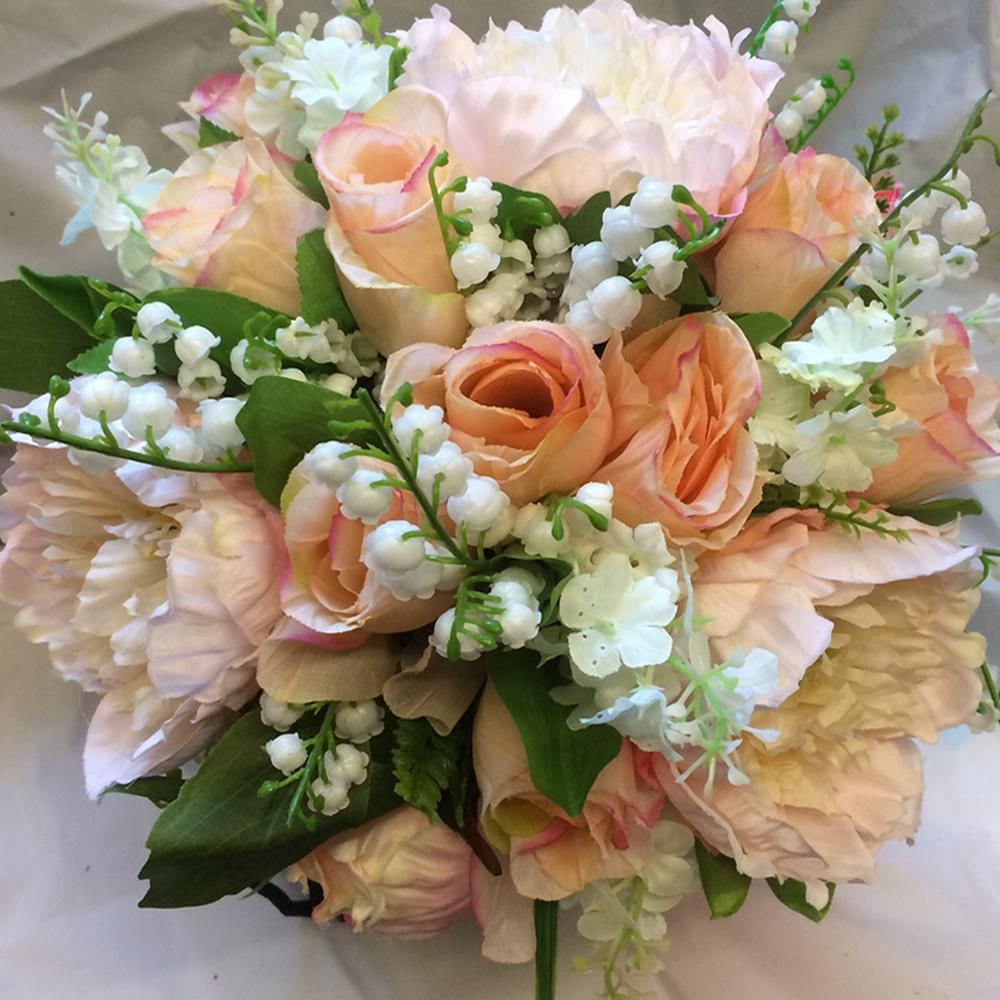 A Wedding Bouquet Featuring Silk Peonies And Roses In Shades Of Pink