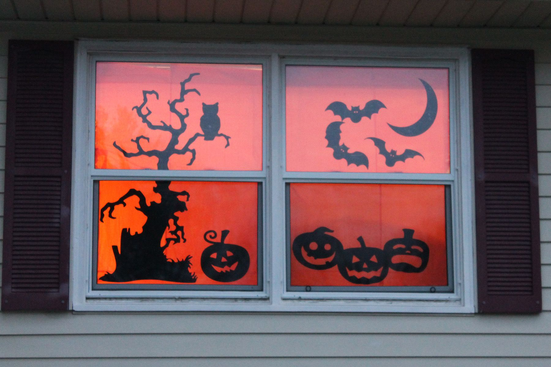 Tape orange tissue paper up behind silhouettes and turn lights on - Window Halloween Decorations