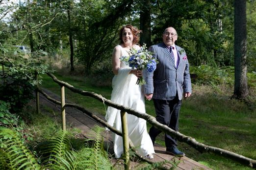 Bride and father walk through woodland at Middle Coombe Farm // Photography by Emma Stoner www.emmastonerweddings.com // The Natural Wedding Company