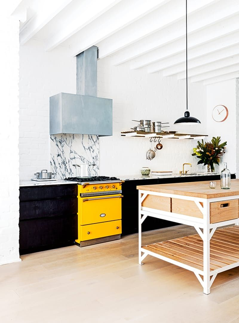 In this kitchen from New Zealand Design Blog, a modern range hood (and a beautiful marble backsplash) pair beautifully with an attention-getting vintage-style yellow oven.