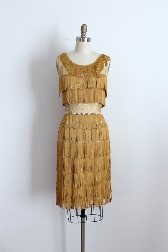 c382a0dbdf3 Incredible gold lurex tassel fringe dress from the early 1960s. This dress  features a flattering silhouette