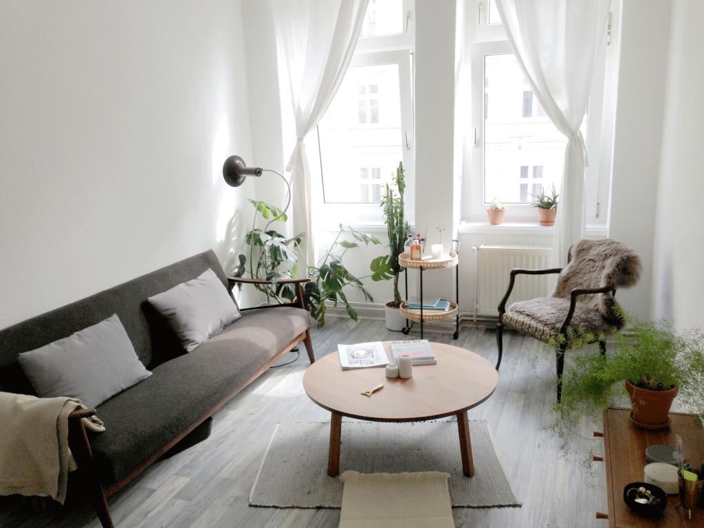 Helles schlicht eingerichtetes Wohnzimmer mit vielen Zimmerpflanzen ...