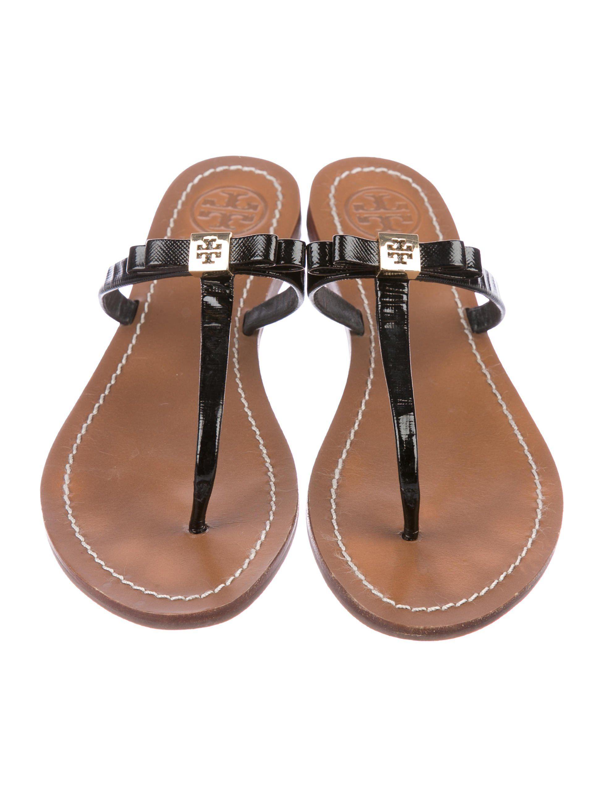 932eeac7a9cc22 Black patent leather Tory Burch thong sandals with bow accents featuring  gold-tone logo embellishments at uppers and stacked heels. Size not listed