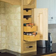 built in spice rack pullout on the countertop with tile backsplash!