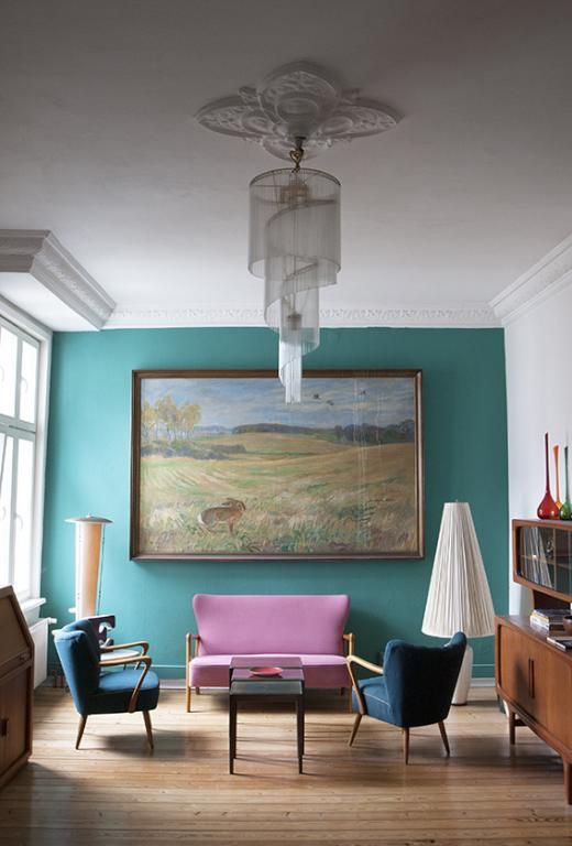Elegantes Wohnzimmer mit Wand in türkis, Wandgemälde sowie farbiger