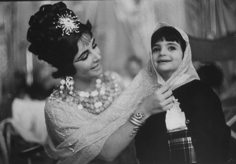 Liz Taylor plays with Liza, her daughter by Mike Todd, while filming <i>Cleopatra</i> in Rome in April 1962. On the set, Taylor famously fell for co-star Richard Burton, who married her and adopted Liza.