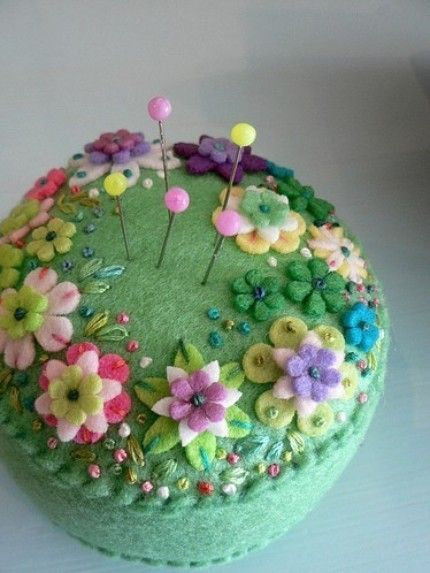 green pincushion with pastel flowers