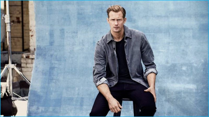 Alexander Skarsgård wears jacket McQ Alexander McQueen, t-shirt James Perse and black denim jeans Brioni.