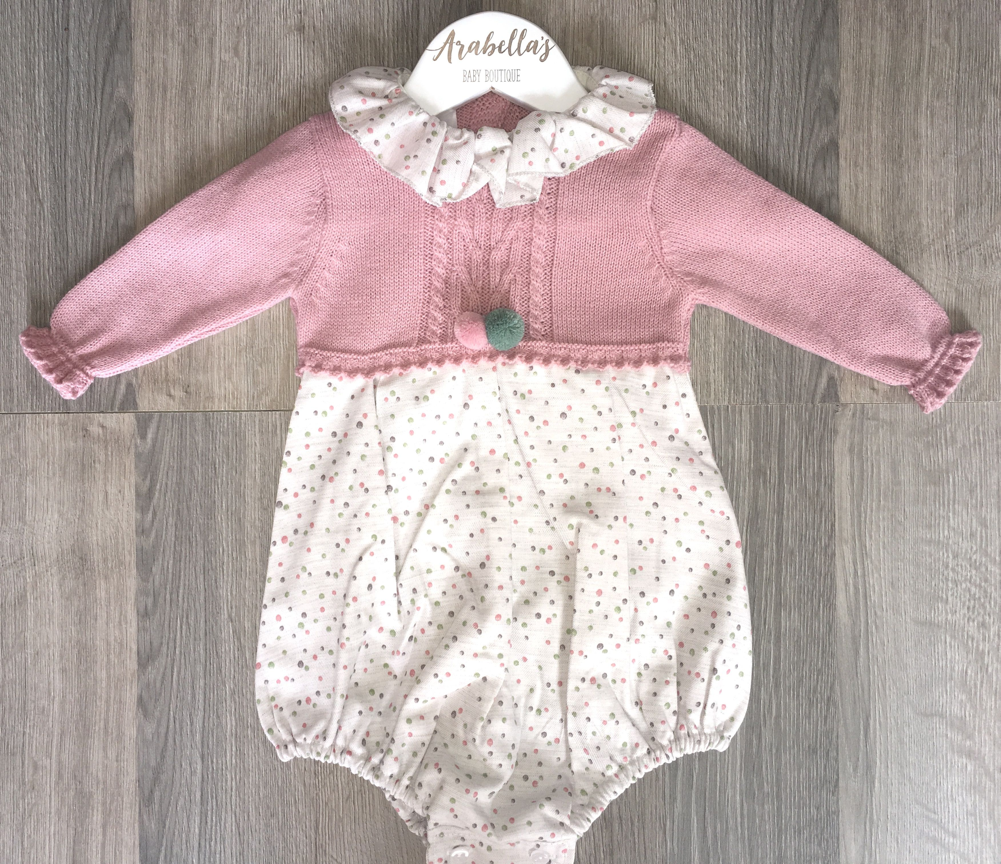 6701a587056 Spanish baby girl romper with pompoms and frill neck. Soft dusky pink  knitted overlay. Spanish baby girls Arabellas Baby Boutique
