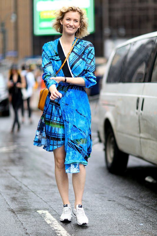 bright blue printed wrap dress with sneakers and a crossbody bag