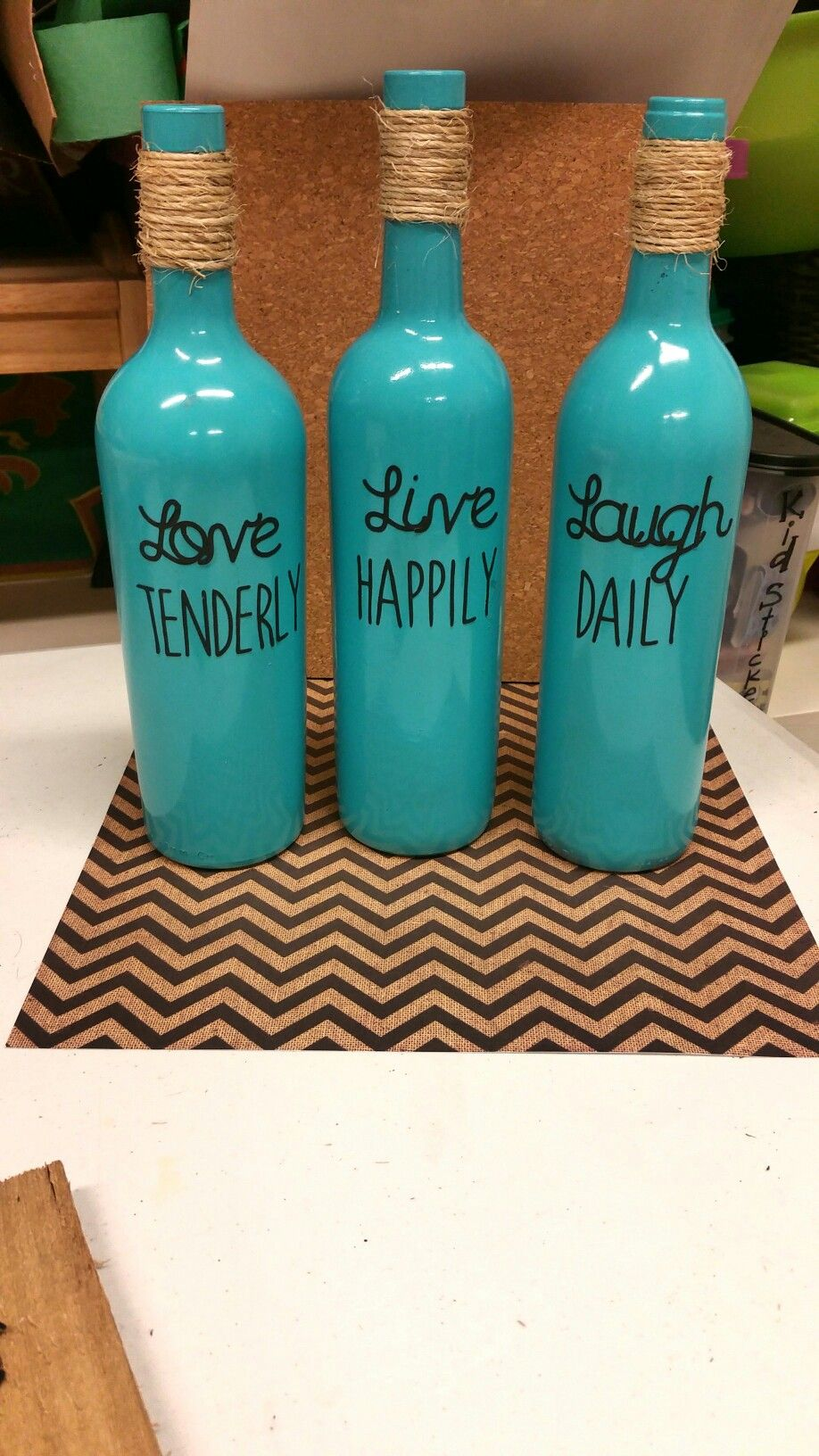 Wine bottles I painted with spray paint and Used My Cricut for the letters.  Spray Adhesive and spray Polyethylene (Decorated Bottle Remove Labels)