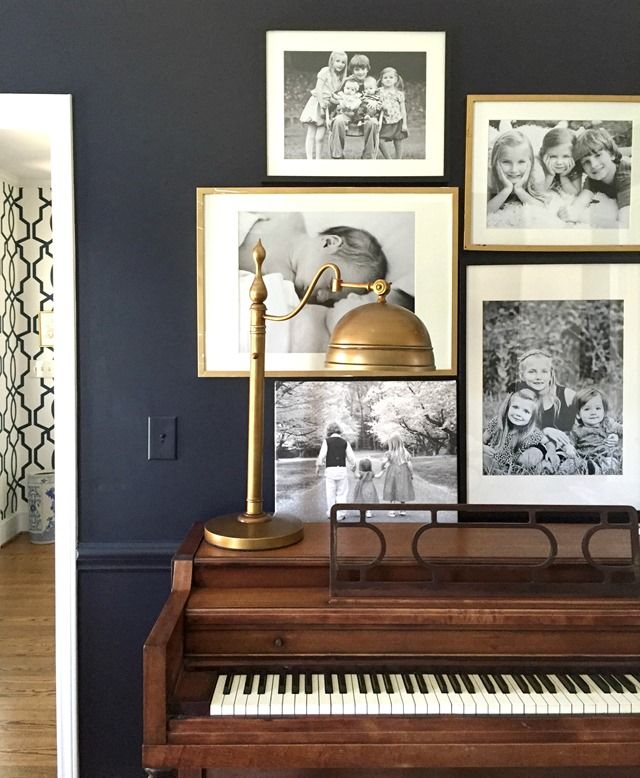 family gallery wall over piano, black walls