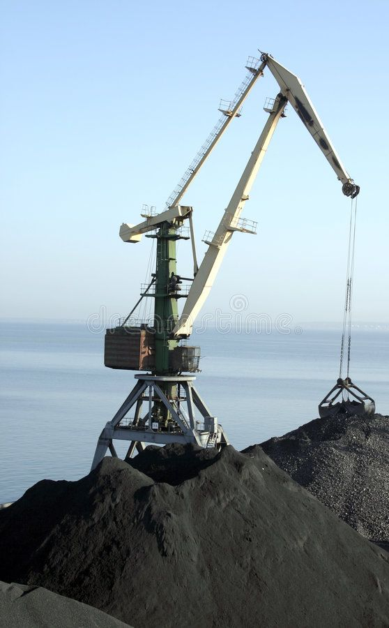 Harbour crane With horizon and coal mountains