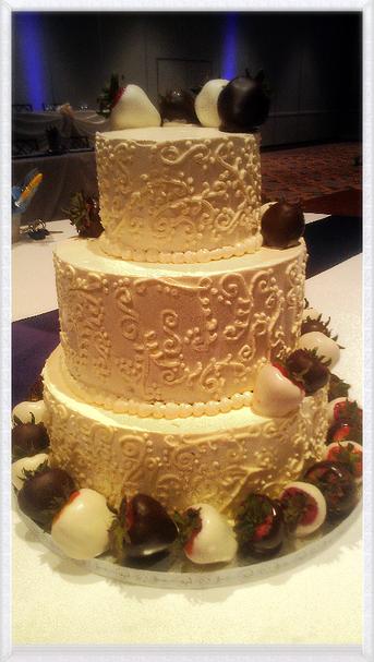 Classic white wedding cake with chocolate covered strawberries