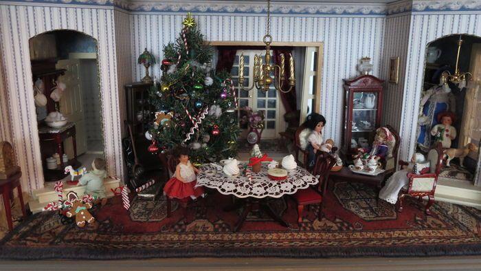 Prachtig poppenhuis Compleet met 8 popjes en hondje, vloerbedekking en gordijnen. 3 kasten met o.a. serviesjes. 1 kroonluchter met kaarsen - 1 hanglamp (niet werkend), stofzuiger - strijkplank - wasmachine - toilet - naaimachine, salon tafel met 3 fauteuils,  eet tafel met 2 stoelen, bureau - piano - site table, badkamermeubel en toilet, kerstboom met toebehoren, (kan echt branden). Poppenhuis kan aan de bovenkant open en dicht, Kan stofvrij afgesloten worden.  I.v.m. het gewicht (met…