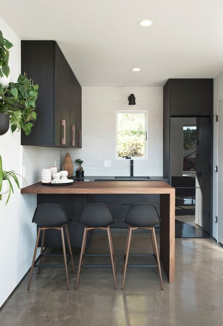 Delightful Kitchen with Peninsula Kitchen Scandinavian Potted Plant Black and White Wall Plants Clean Lines Bar Stools Waterfall Countertop House Tall Cabinets Breakfast Faucet #waterfallcountertop