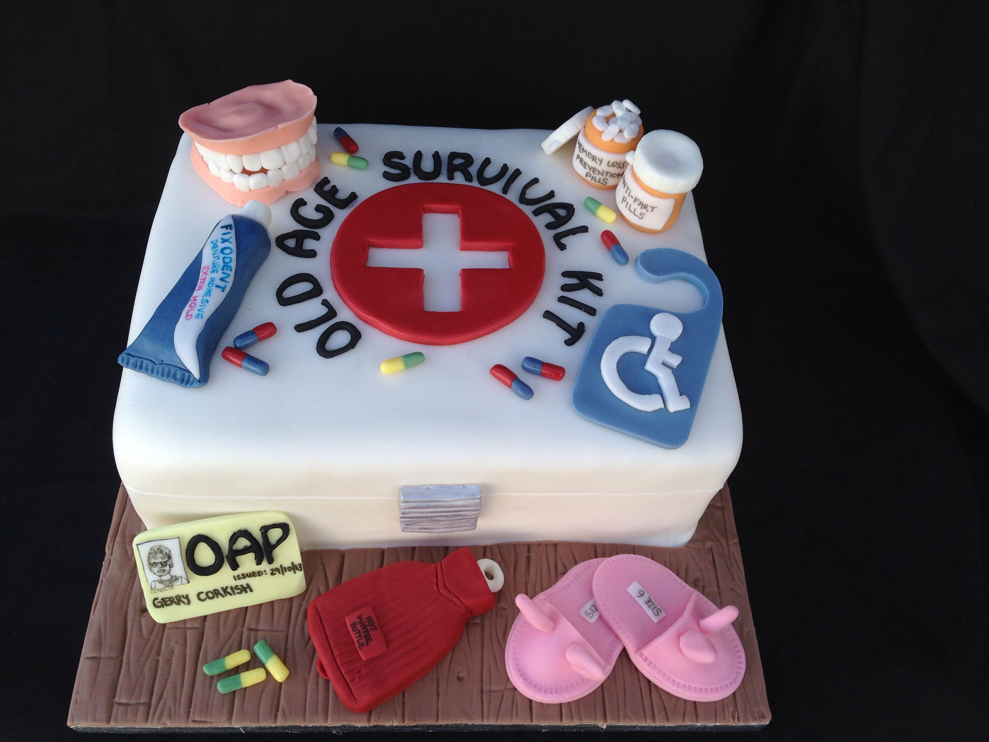 Old Age Pensioners Survival Kit - birthday cake. Fondant dentures, fondant bunny slippers and fondant survival box all hand crafted.