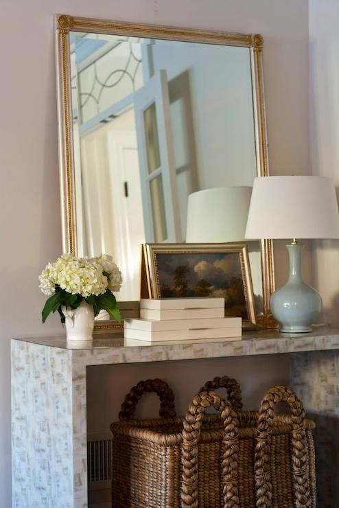 Chic Foyer With Large Woven Basket Tucked Under Stone Waterfall Console Table Filled Silver