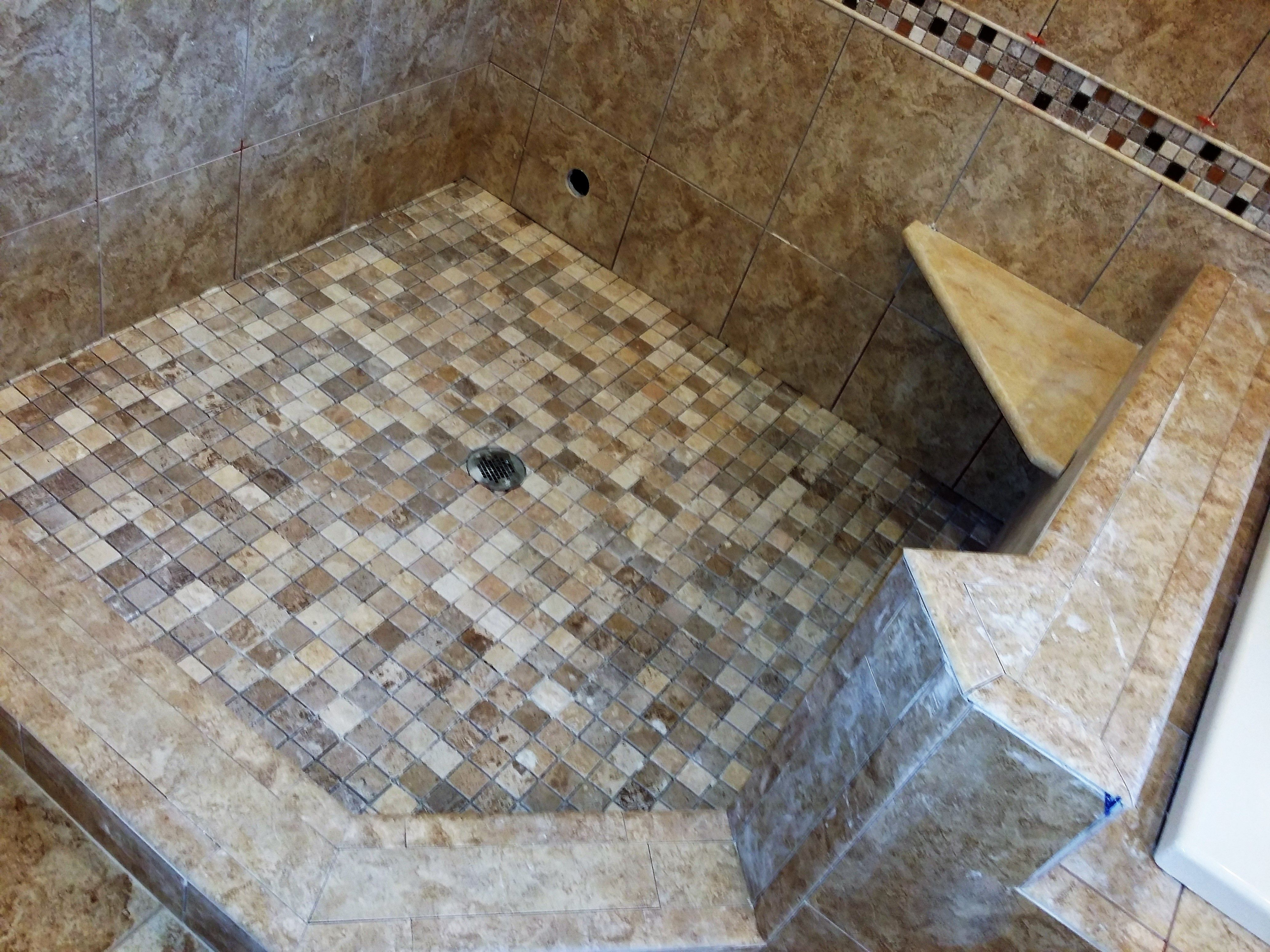 Mosaic shower tile floor with corner seat knee wall and accent tile