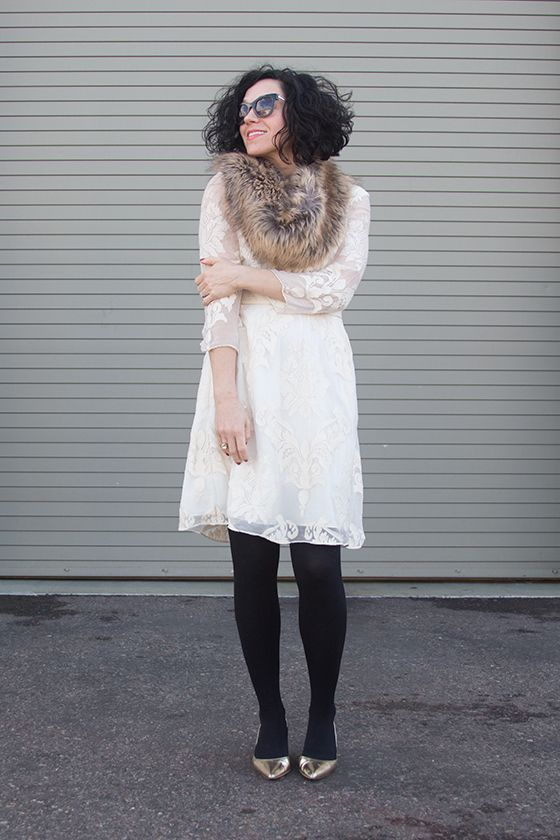 Tan faux fur infinity scarf, white dress with brocade print and sheer sleeves, black tights, and gold metallic heels