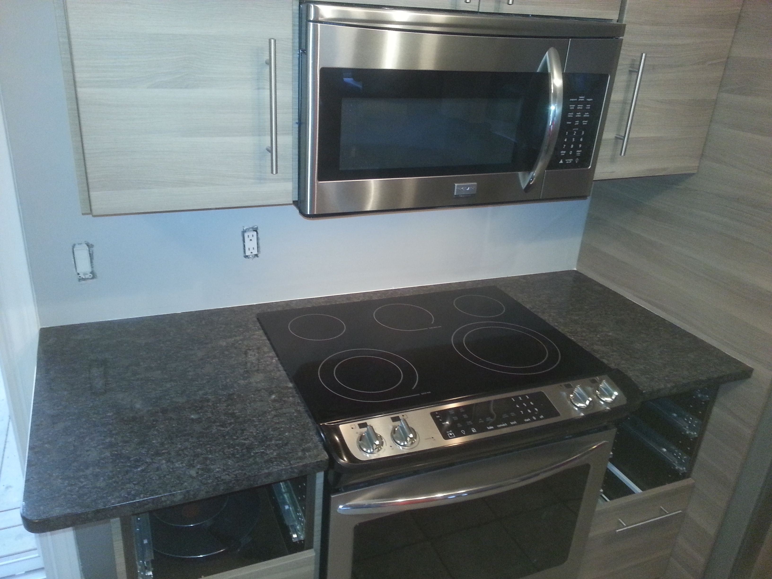 Attirant Steel Grey Granite Countertops, Including Stove Bridge, Wrapped Around A  Slide In Range.