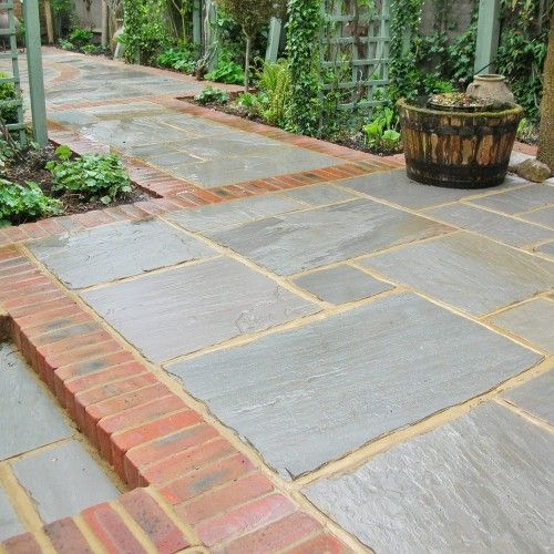 Stacked Grey Brick Stone Patio With Green Grass Yard And Green