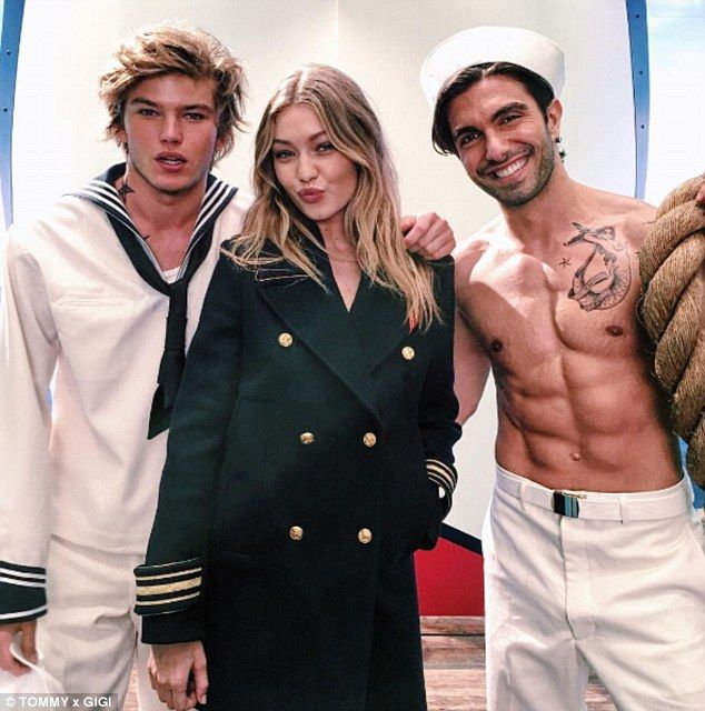 Center of attention: The 21-year-old supermodel poses with hunky sailors in the images, se...