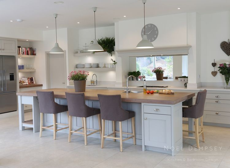 The Wicklow mountains provide a stunning backdrop for this Plain English Kitchen. The simplicity of the shaker doors combined with the chunky floating shelves give the design a more contemporary look. The white Silestone worktops are scratch and stain resistant to ensure they look like new for years to come. The contrasting stained Oak surface on the Island brings in a lovely warm texture into the design. Designed by David Dempsey #plainenglishkitchen The Wicklow mountains provide a stunning bac #plainenglishkitchen