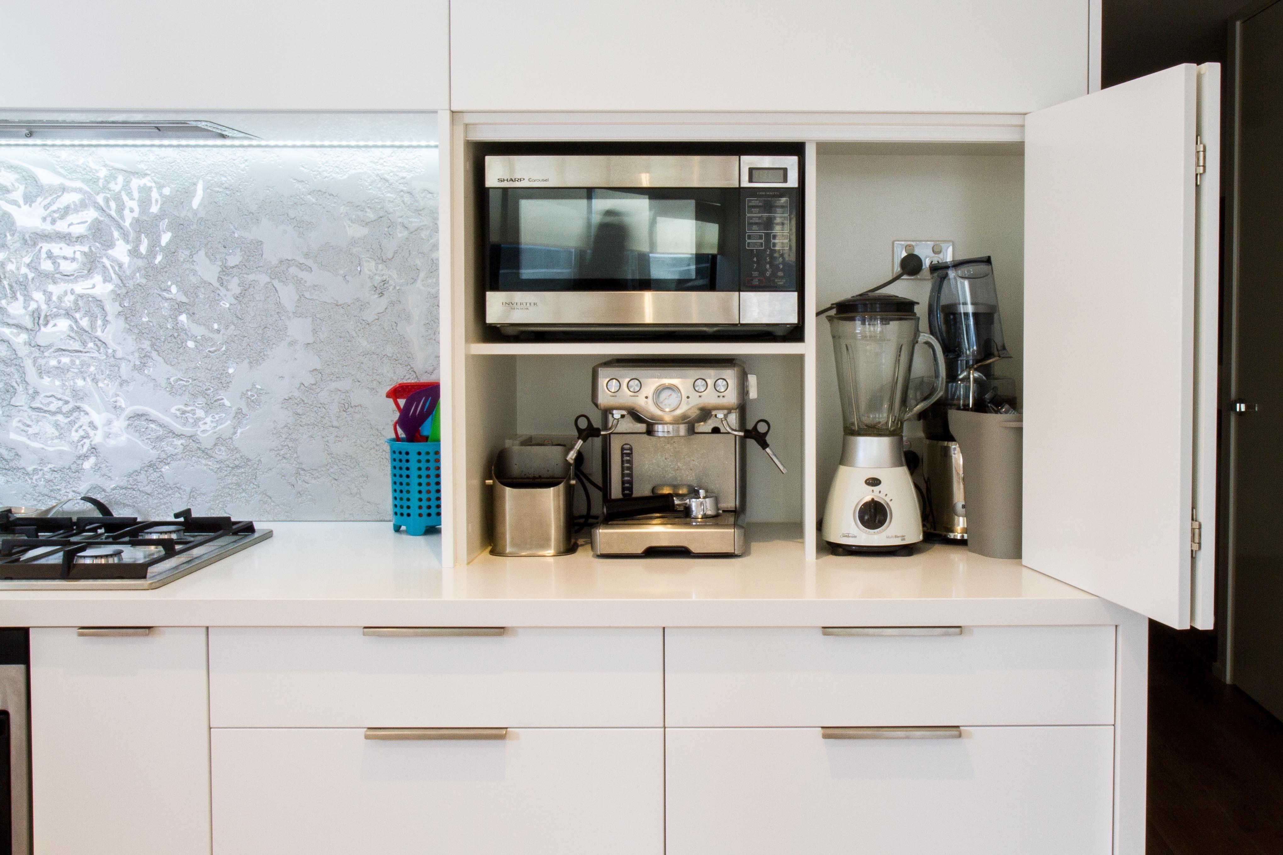 Appliance pantry. Bi-fold doors. White modern kitchen. www