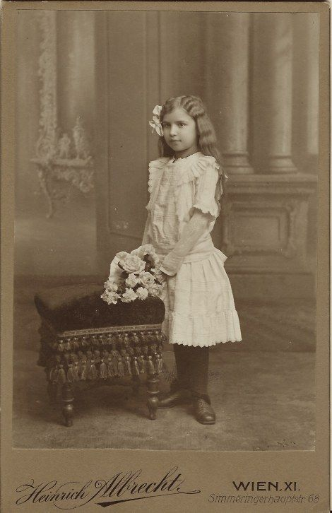 This cabinet card features a portrait of a very pretty young girl from Vienna, Austria dressed in fine clothing and holding a bouquet of flowers. Her hair is styled for her day at the photographer and she is wearing a hair bow.