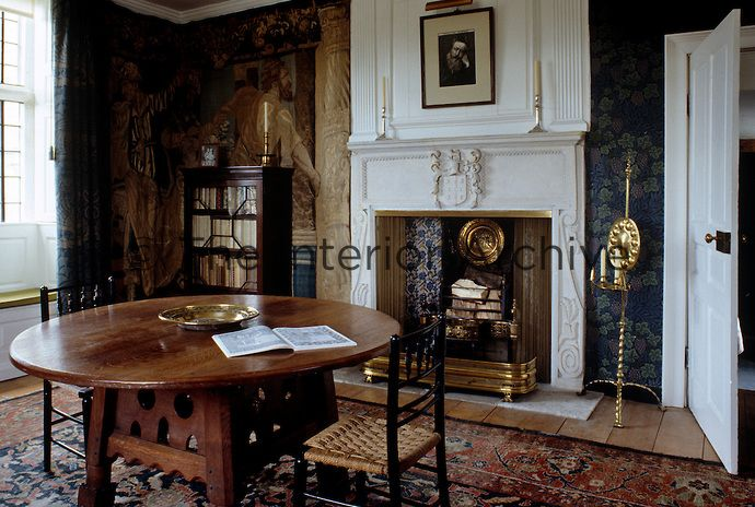 The study at Kelmscott Manor, the Arts and Crafts house of William Morris in Gloucestershire where the hand-blocked wallpaper and sturdy circular table are classic examples of his style