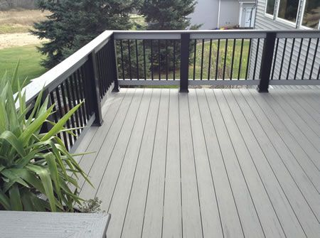 A Composite Wood Deck With A Light Grey Color And A Nice Railing