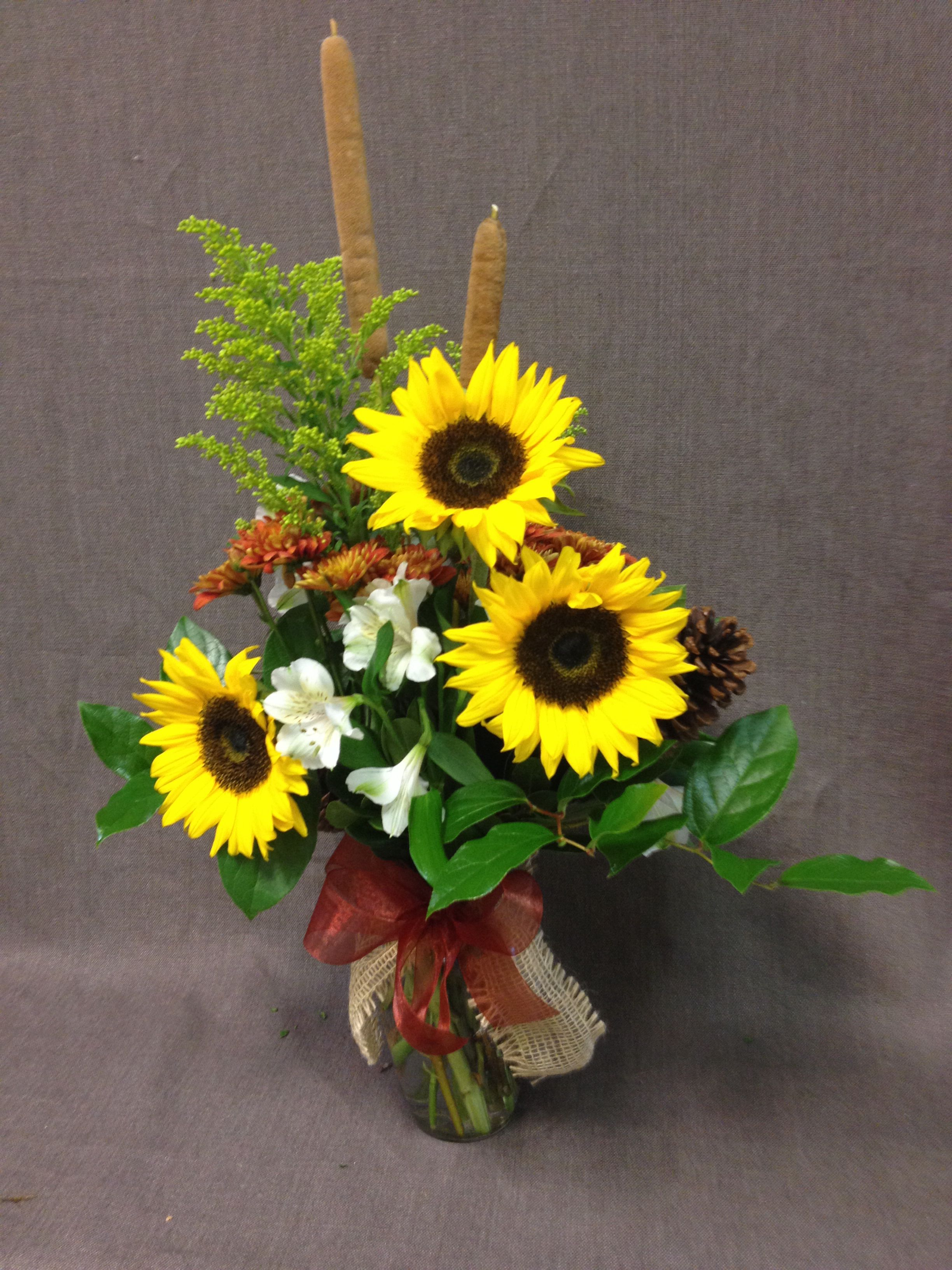 Arrangement at work with sunflowers cat tails and pine