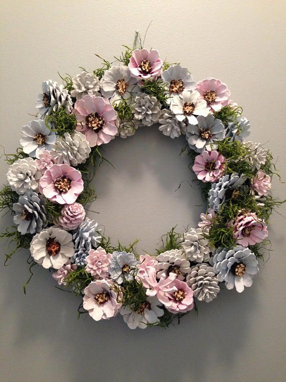 This unique pine cone wreath in shades of blue, gray, pink and white would make a lovely house-warming gift or brighten up your own home. Each pine cone is hand painted and wired and measures 13.5 x 13.5. Sprayed with a water-resistant acrylic spray, this wreath will withstand the outdoors but preferable under a covered porch.