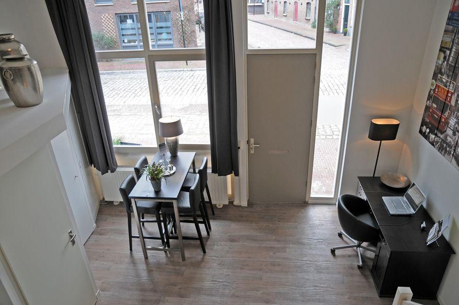 www.debergpoort.nl Je eigen prive bed and breakfast in deventer met twee etages. Vanuit de lounge kijk je neer op het eetgedeelte, de keuken en het bureau met laptop.