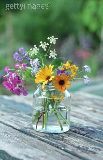 A Glass Jam Jar Containing A Mixture Of Wildflowers And