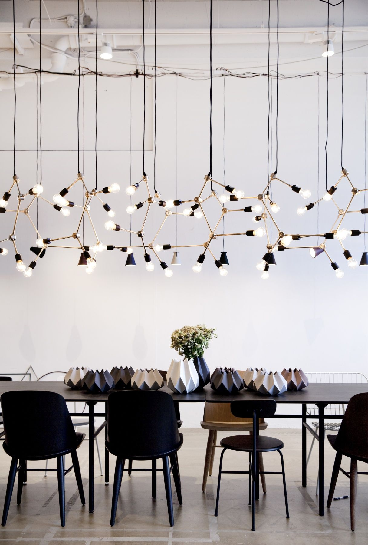 Modern Lighting Installation With Black Table And Chairs
