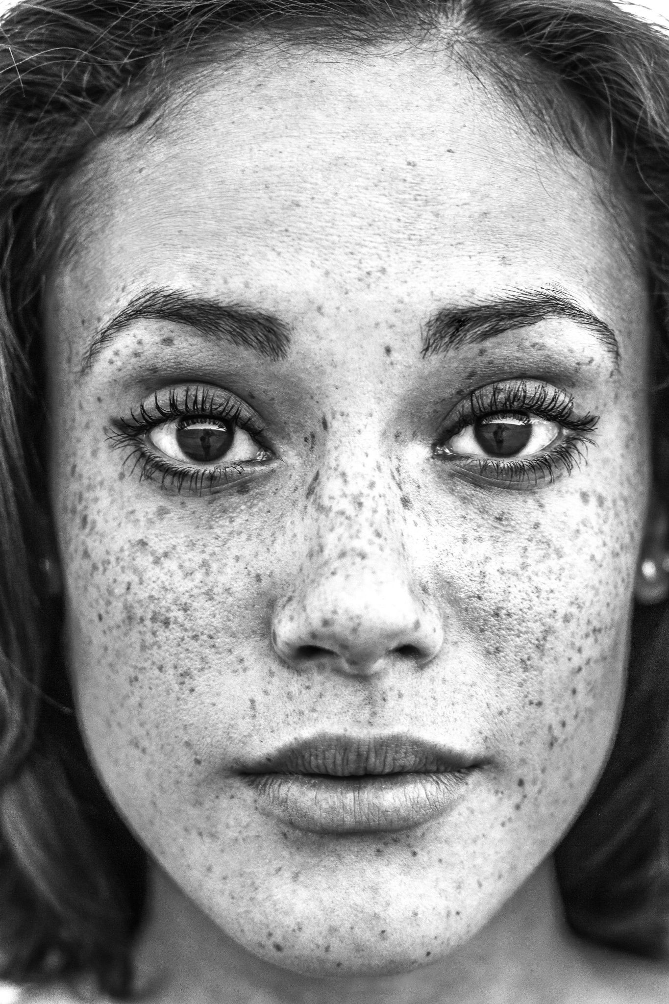 Freckle portrait black and white black and white close up portrait of beautiful female face with freckles gorgeous eyes and lips and a serene look